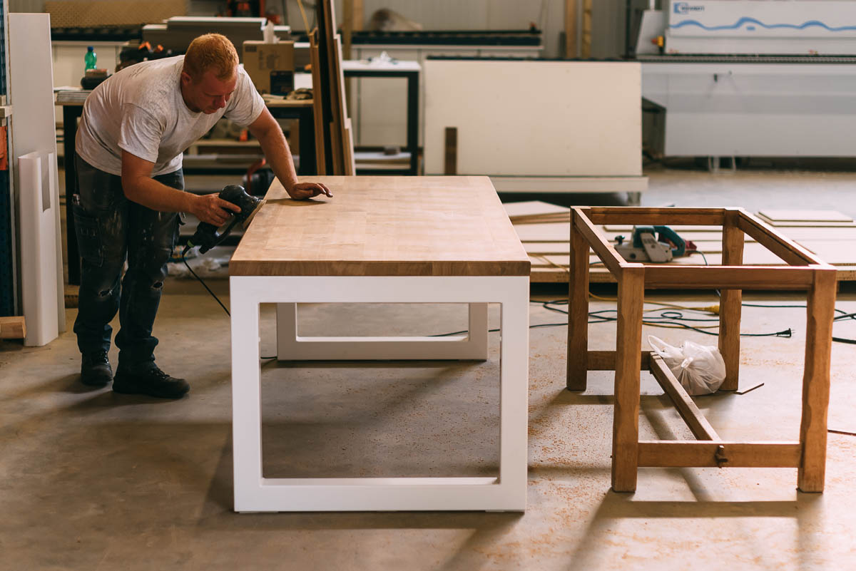Nieuw en oud tafel onderstel naast elkaar. Van massief eiken naar wit gelakt stalen frame.